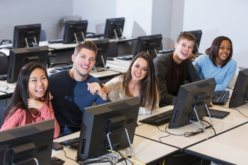 Completing the Circle - Five young people sitting in a row and smiling in a computer lab.