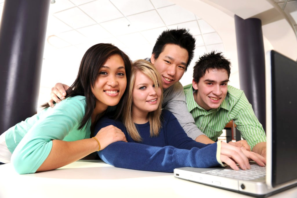 Youth Job Link Program - Diverse college student friends at a laptop.
