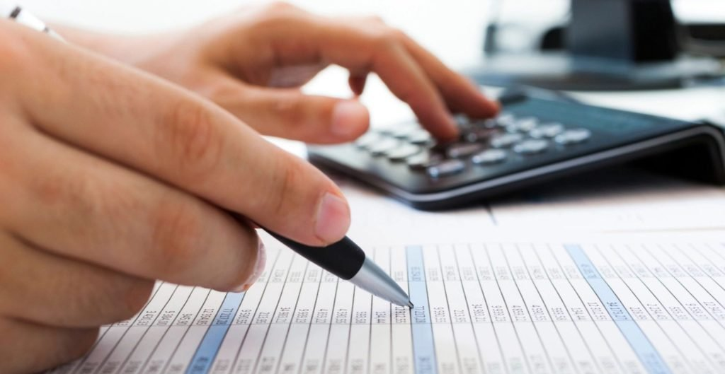 Financial Education - A person crunching numbers using a calculator.