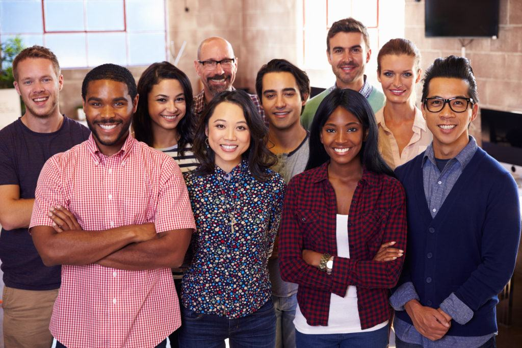 Client Success Stories - Portrait of multicultural staff standing and smiling in a modern design office.