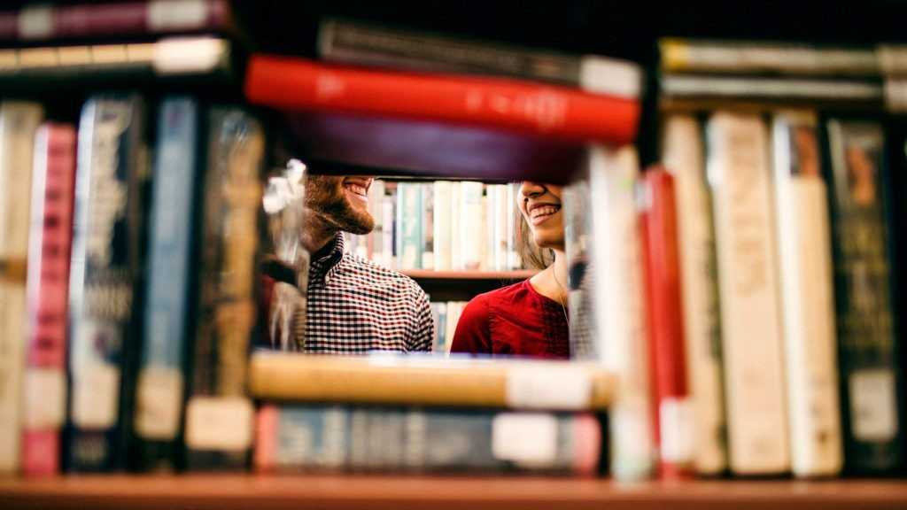 Learning Library - Two people smiling at each other, as seen through a frame of books in a library.